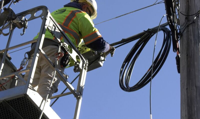AT&T technician working with cables on a utility pole.