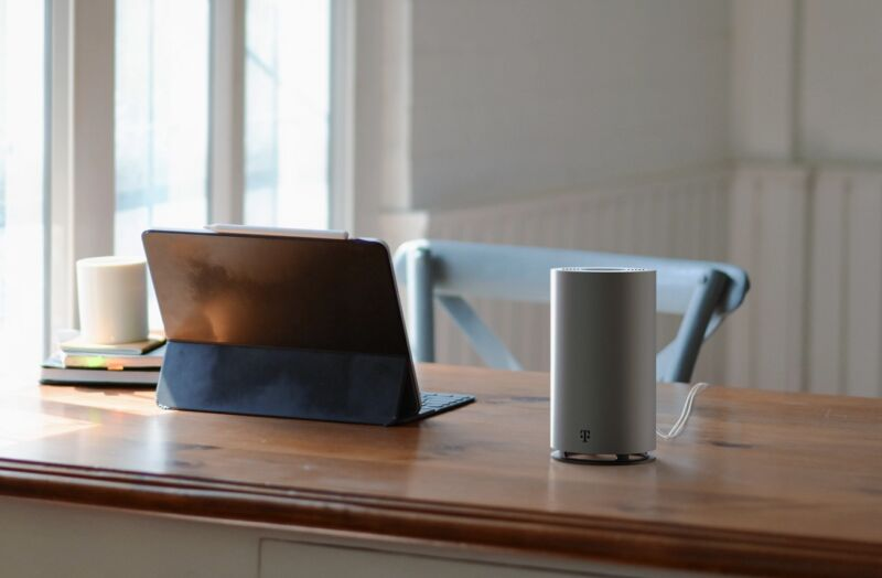 T-Mobile's 5G home Internet gateway sitting on a desk next to a tablet.