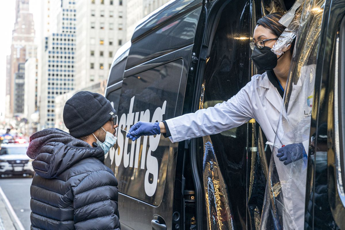 A person in a lab coat and latex gloves leans out of a van to take a nasal swab of a person standing beside the van.